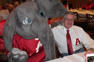 Big Al Elephant and man in white shirt and red tie siting at table.