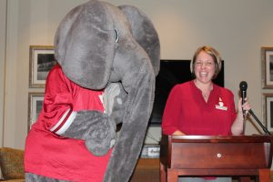 Big AL Elephant standing by lady in red shirt behind podium..