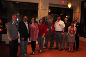 Group of people standing with Big AL Elephant in room with dim light.