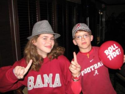Girl in red BAMA shirt and Boy in Red Football shirt in dim light room.