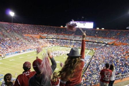 Fans standing in stadium at football game.