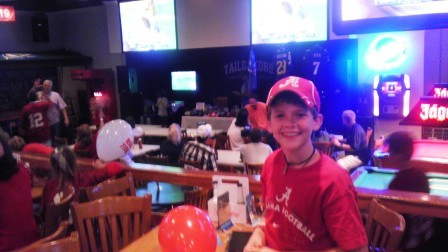 Boy in red shirt and red cap standing by a table.