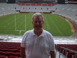 Man standing in football stadium.