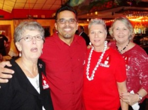 Four people standing in room with red ceiling.