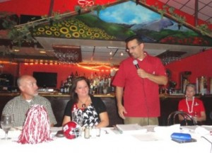Three people sitting at table with white cloth and one person with microphone in red shirt.