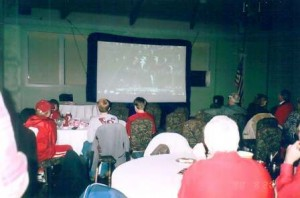 Group of people in room with screen in background.