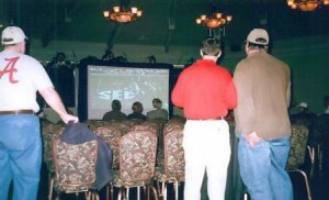 People in a dim lit room watching a football on a large tv screen