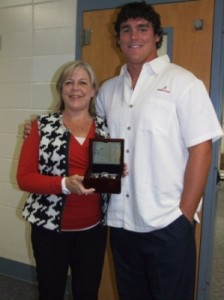 lady with black and white vest and red shirt holding a plaque and man white shirt.