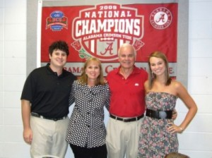 Group of people standing in front of red national champions banner.