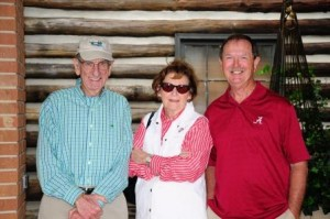 Three people standing in front of log wall.
