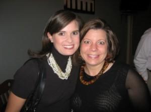 Two ladies n black dress standing in dark room.