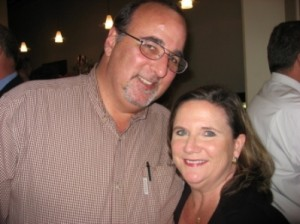 Man in beige shirt and lady in black top standing in dark room.