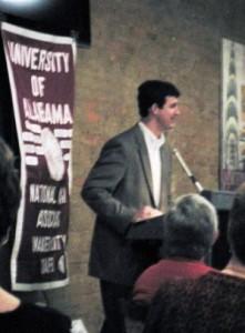 Man at Podium speaking with crimson banner in background.