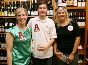 Three people standing in room with wine display in background.