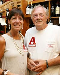 Lady in white top and man in white shirt standing in room.