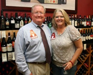 Man in blue shirt and dark tie and lady in gray top standing in front of wine display.