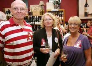 Group of people standing in front of wine display.