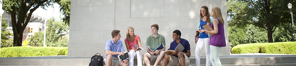 6 students talking at the base of Denny Chimes