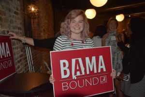 lady holding a red Bama Bound sign