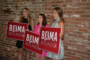 three students holding red Bama Bound signs