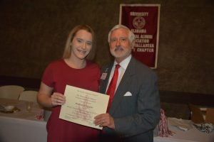 girl in red dress and man in gray suit holding certificate