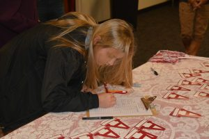 Lady signing paper at red and white table.