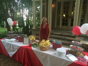 One lady standing outside in front of food table with red and white cloth.
