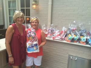 Two ladies standing outside in front of white brick wall holding a gift basket.