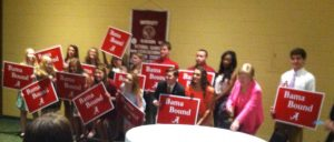 Group of Students holding red signs in front of gold wall.