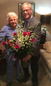 Man and Women holding an arrangement of flowers.