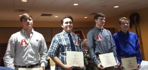 Three male students holding certificates