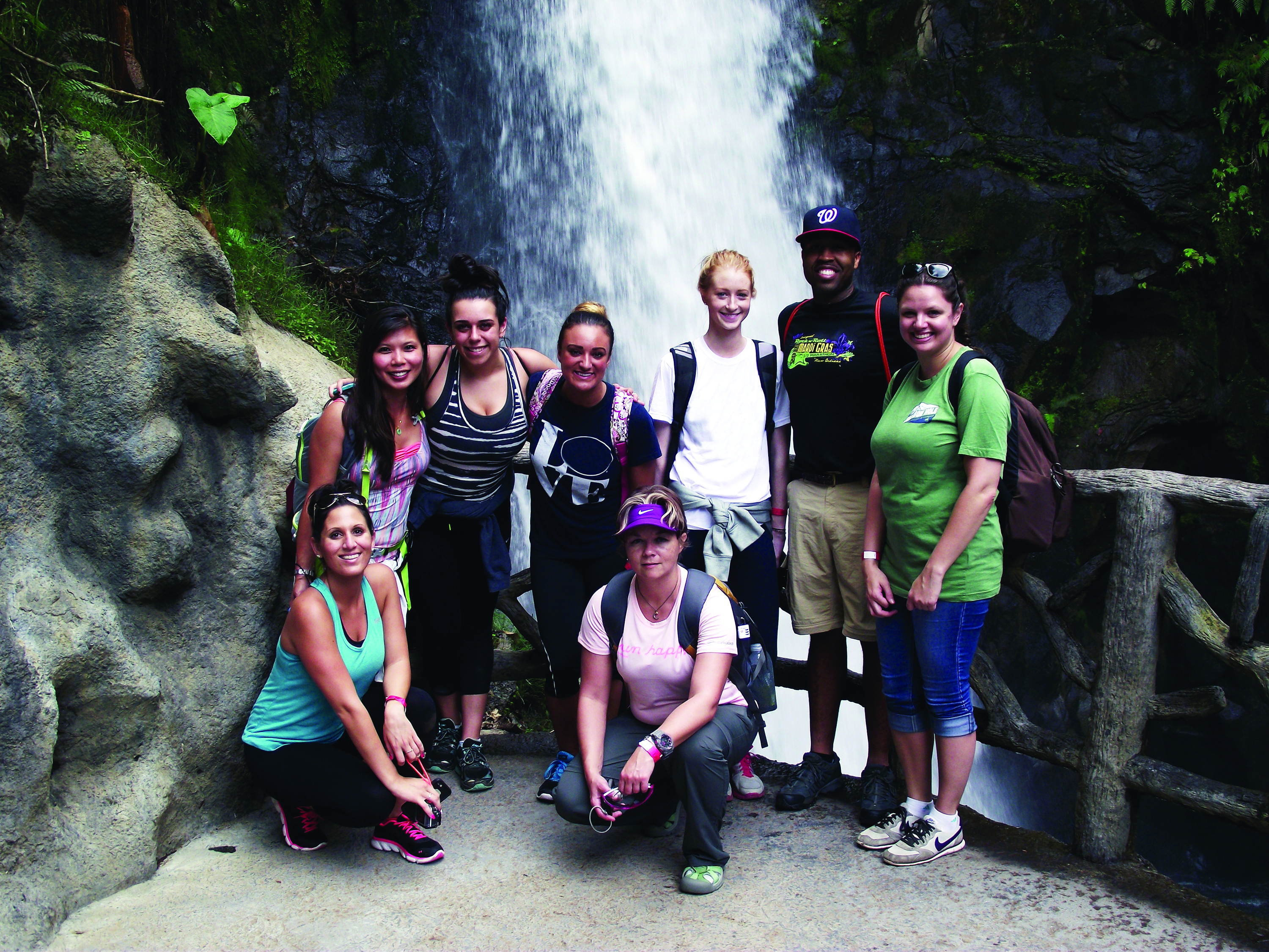 A group of people posing in front of a waterfall