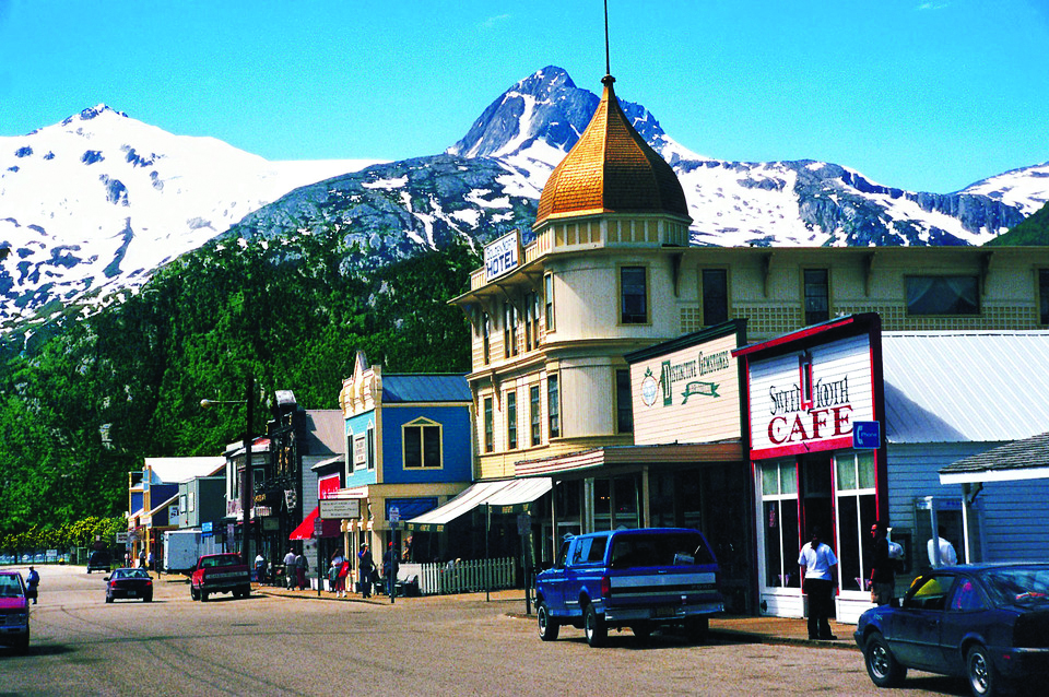 A small town main street in Alaska with mountains in the background