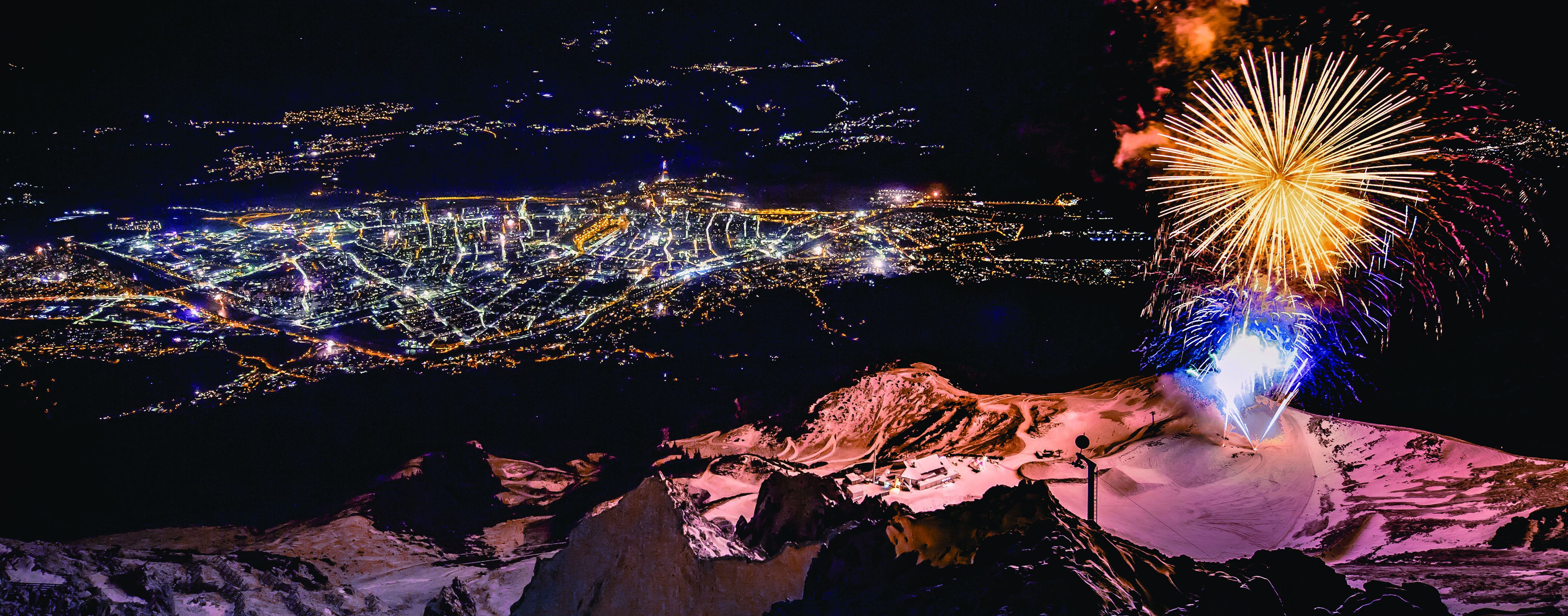 Fireworks exploding over a mountain at night with a lit city below