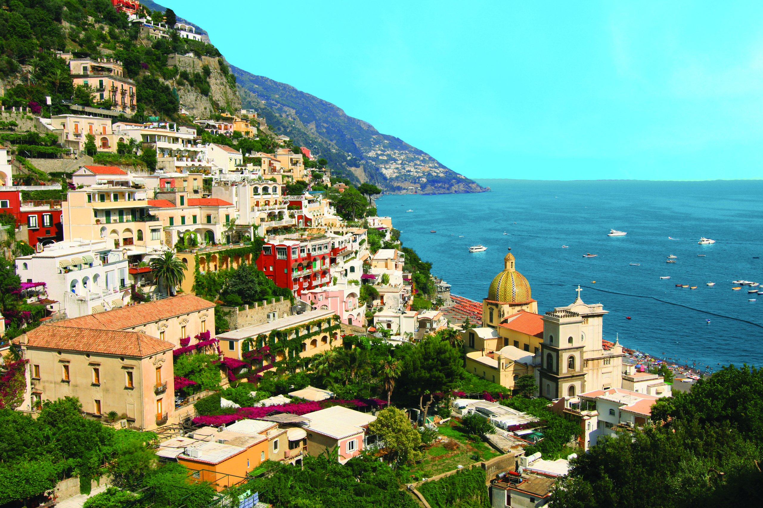 Colorful buildings built into a mountain overlooking the coast.
