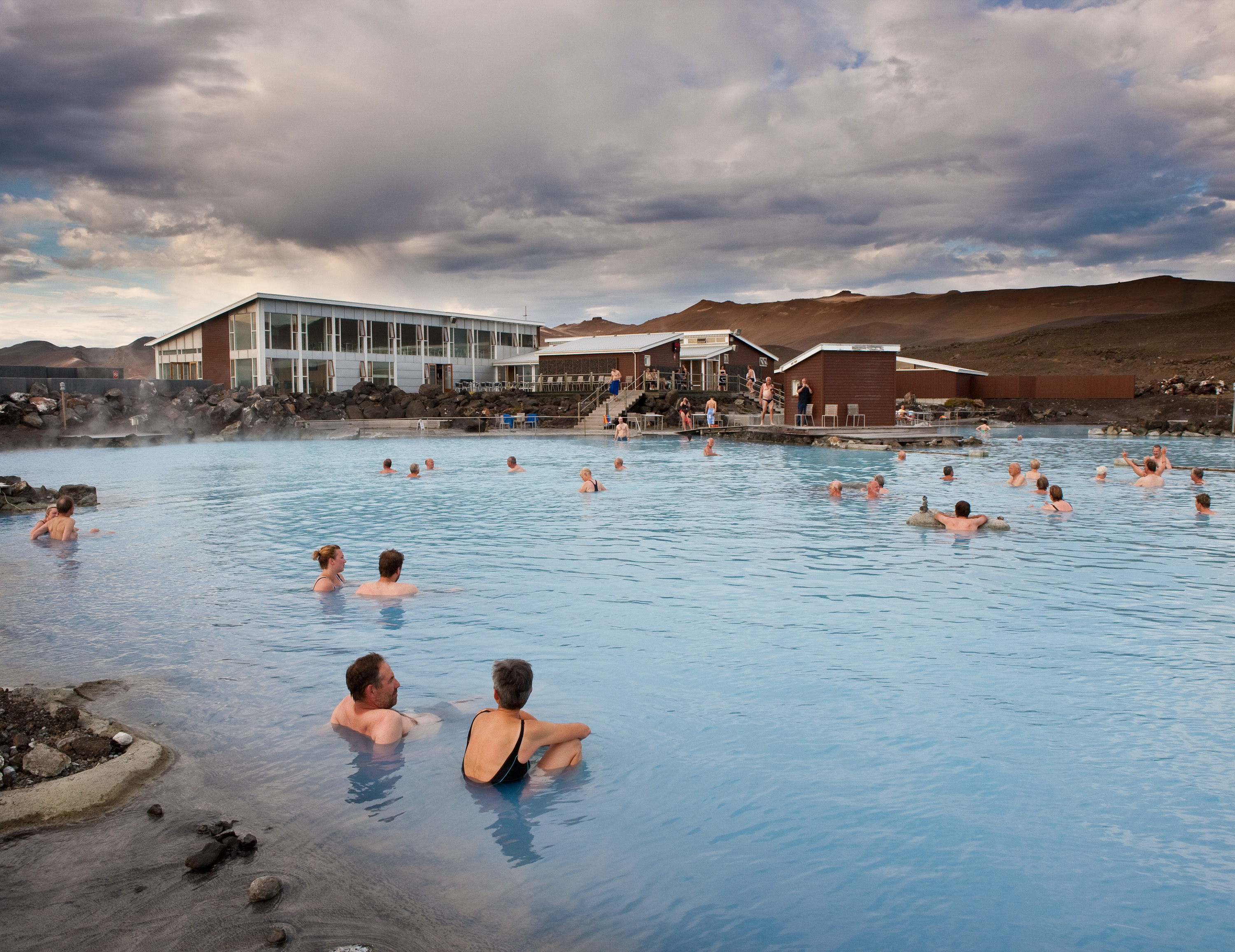 People relax in a natural blue pool under a blue sky.