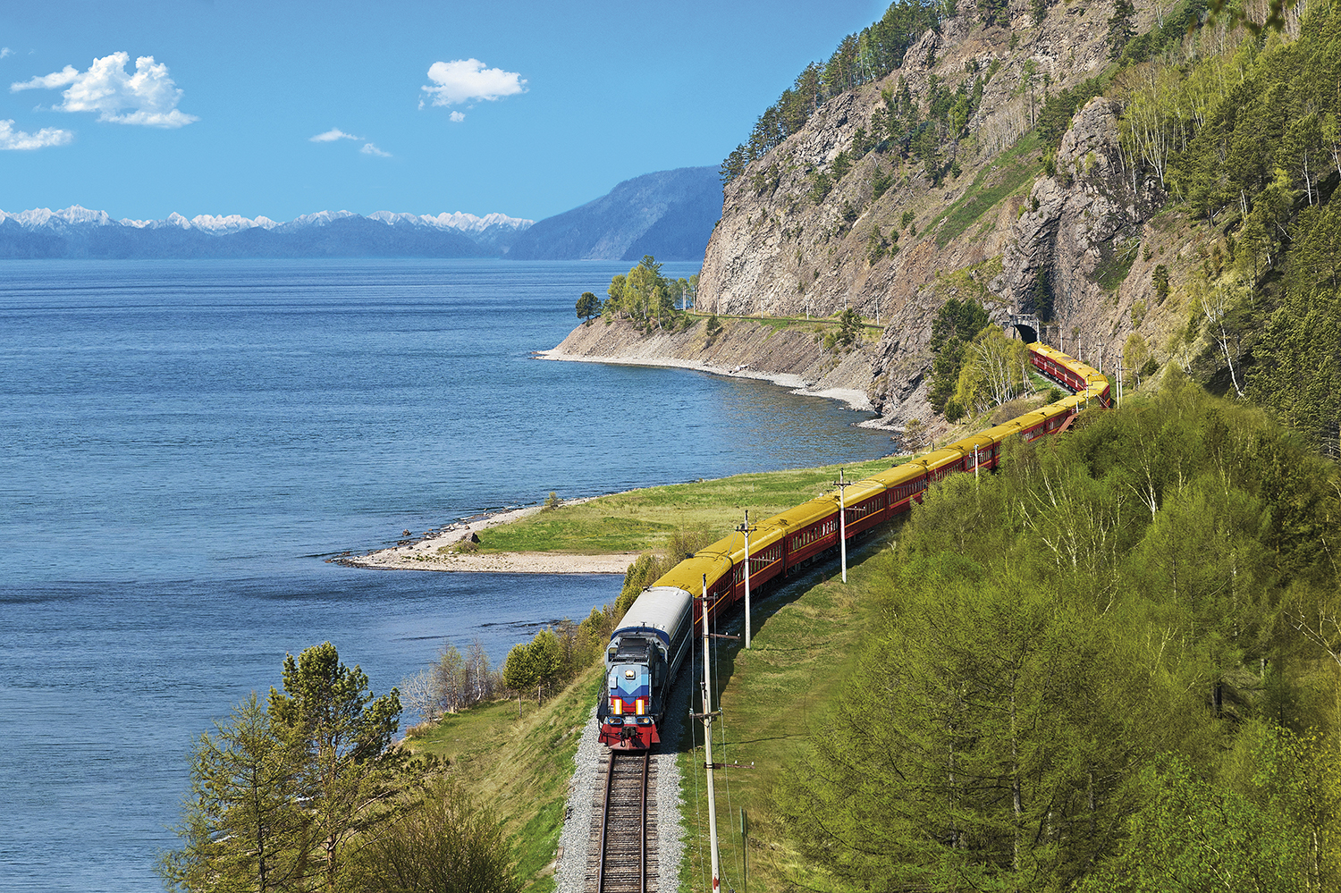 A locomotive follows a winding track separating the shore from green mountain.