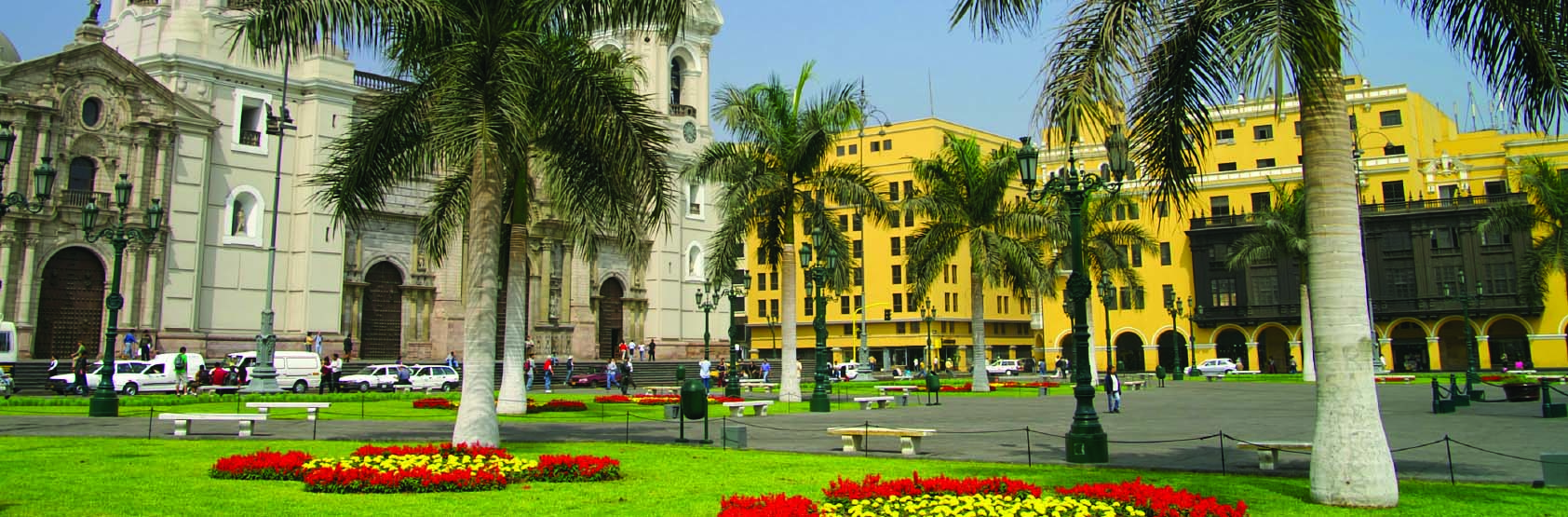 A breathtaking cathedral in a town square surrounded by an aboundance of palm treees and native red flowers