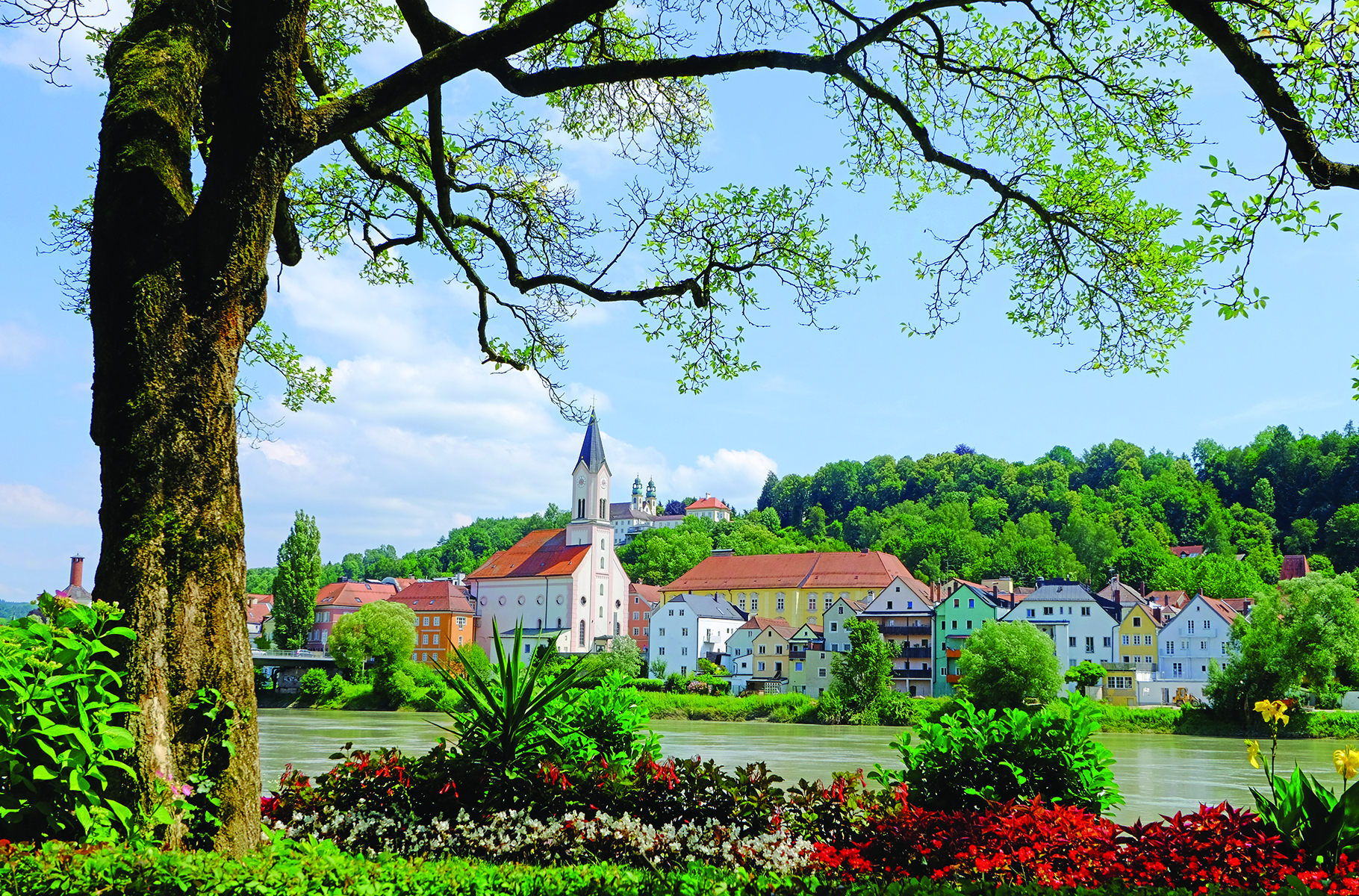 Town surrounded by greenery with homes and churches.