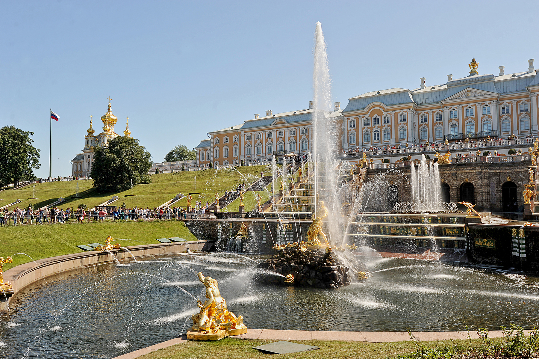 A Gold accented Fountain sits below a beautiful palace on a green lawn.