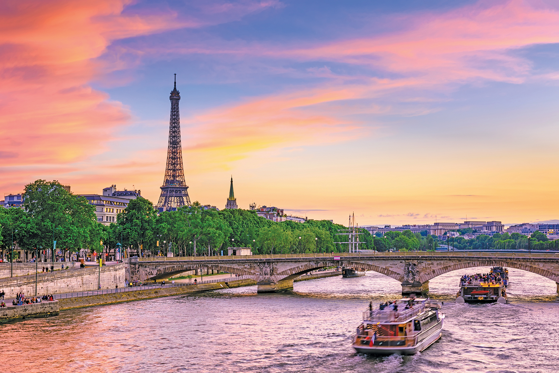 Sun Sets behind the Eiffel Tower. Bridge that overpasses the Seine River.