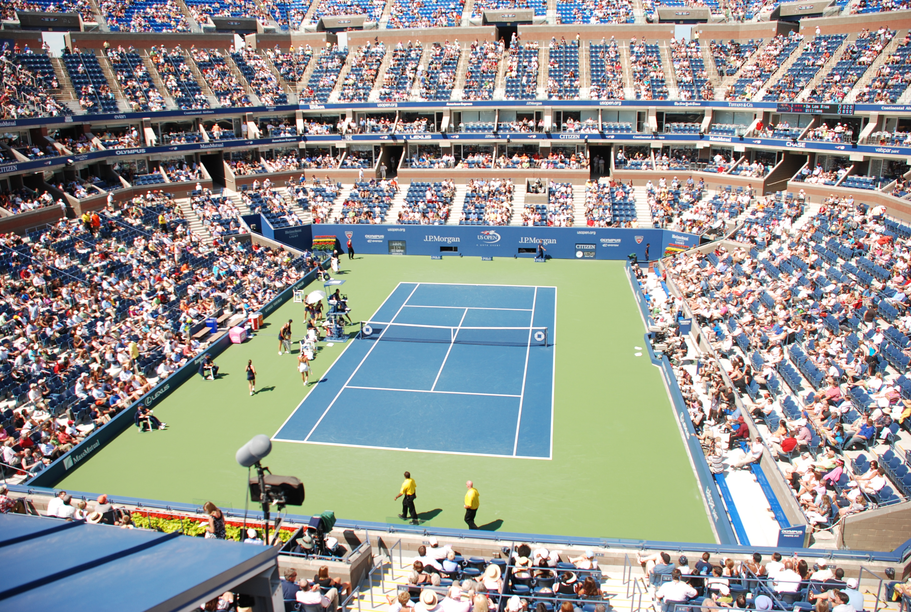 Crowded arena for tennis match on a blue court.