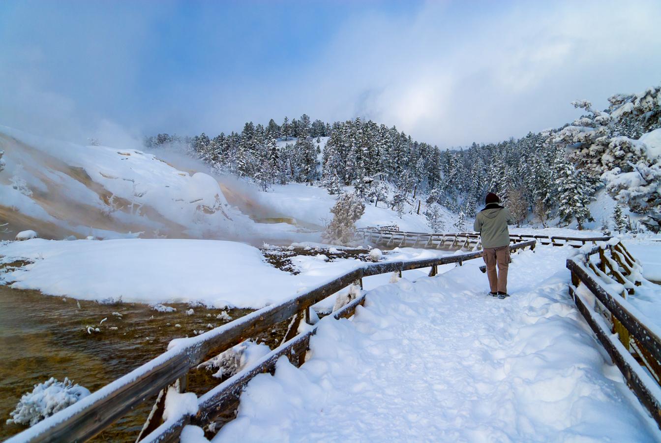 A man walks along a snowy trail